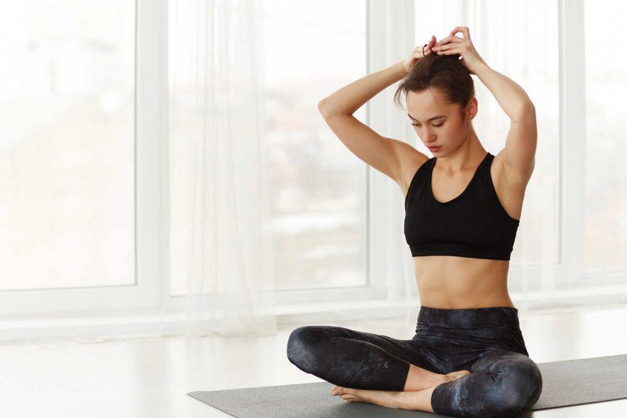 yogi-woman-tying-hair-before-workout-at-yoga-studi-KHFND7F.jpg